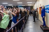 A group of Hillary Clinton supporters turn their backs to her en masse to take selfies as she waves to them in Orlando, Florida.