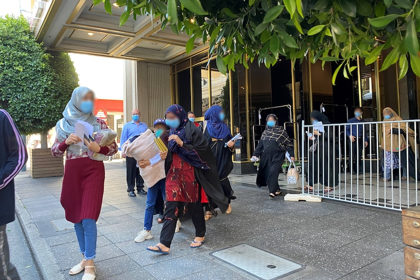 Women wearing headscarves walk out of the front doors of a hotel