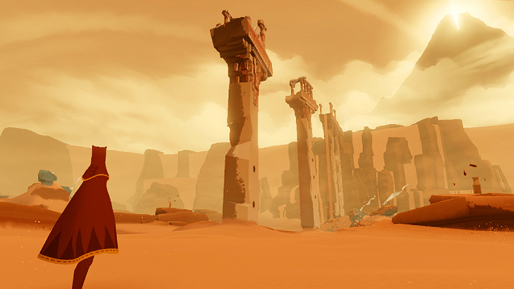 In a scene from a video game a lone caped figure stands in yellow hued desert landscape and looks up at tall ancient ruins.