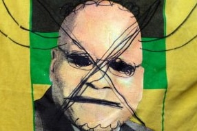 A photo of Former President Jacob Zuma on the South African flag has been crossed out and horns drawn on his head.