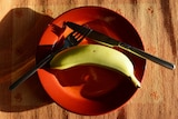 Banana on a red plate with a knife and fork resting on the plate near it.