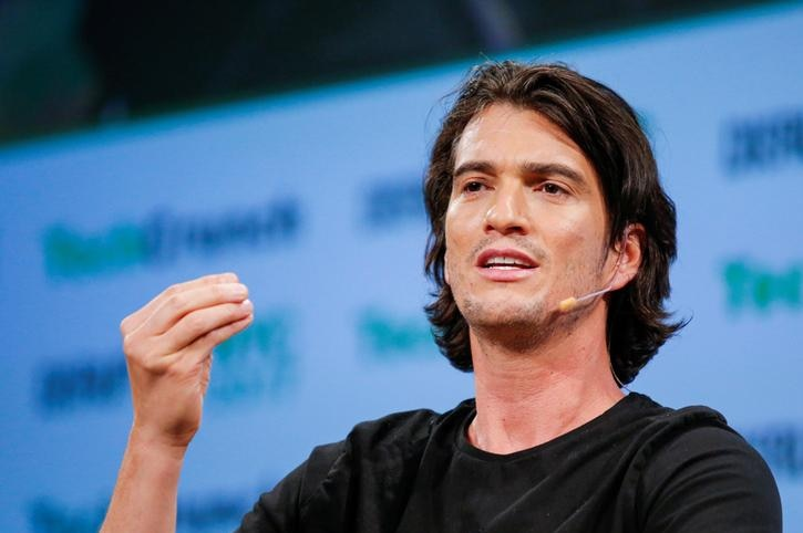 Adam Neumann gestures with one hand while speaking with a microphone next to his mouth. He appears in front of a blue background