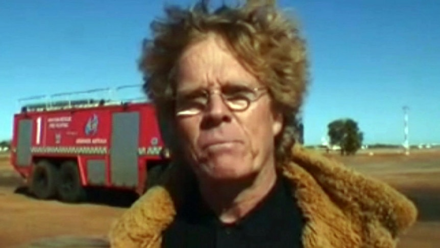 A close-up of face of a man with curly red hair who is standing outside in front of a fire truck
