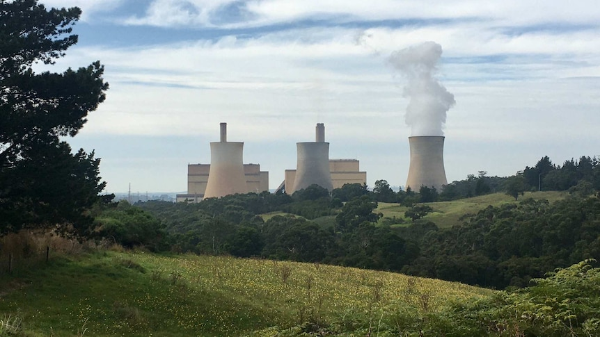 A  large power plant blowing smoke with green rolling hills in the foreground.