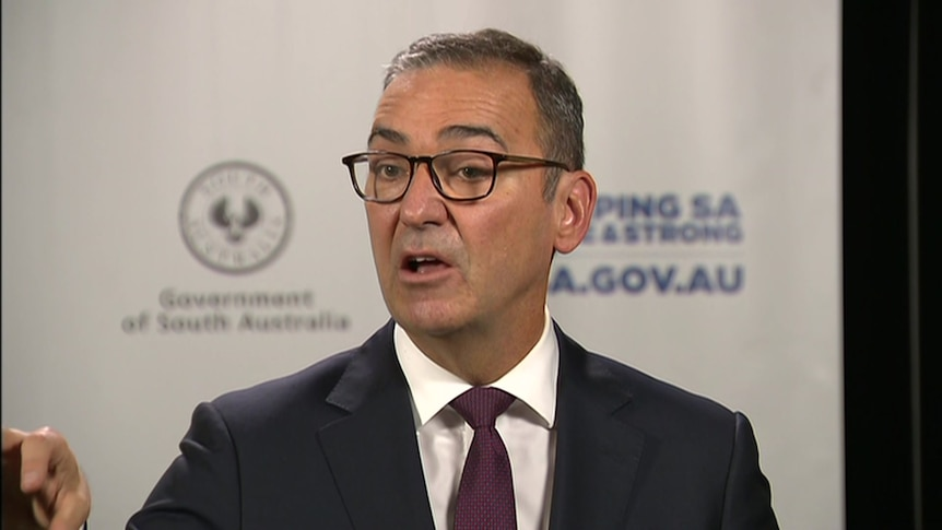 Steven Marshall stands in a suit in front of a SA Health and SA Government logo background