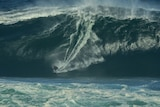 A surfer carves down the face of an enormous, heavy wave in WA.