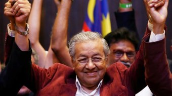 Mahathir holds his hands up in celebration.