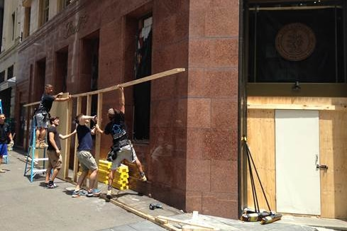 Workers repair the exterior of the Lindt cafe