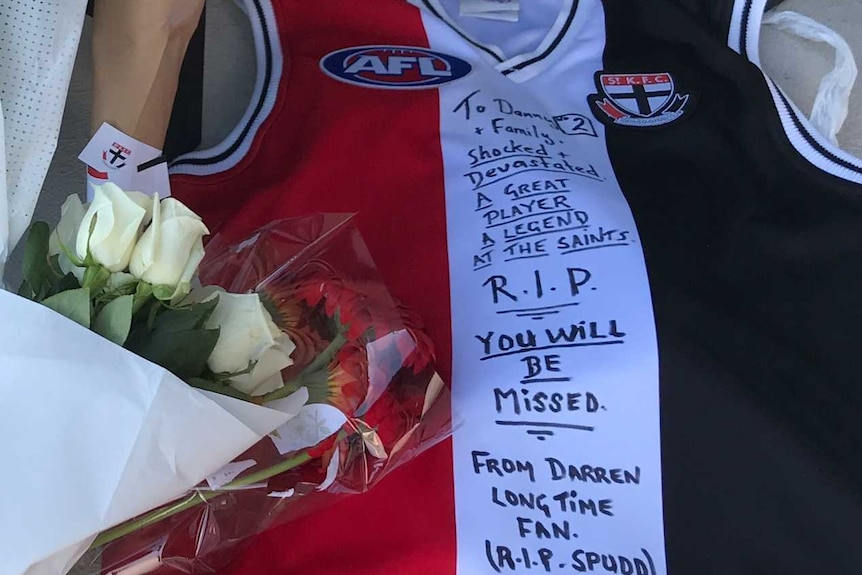 Bouquets of flowers and a signed St Kilda vest lie outside the St Kilda Football Club headquarters.