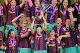 Barcelona players celebrate wildly as Vicky Losada holds up the Champions League trophy