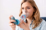 Asthmatic woman using inhaler with spacer
