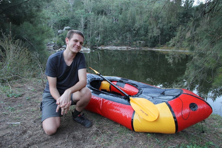 21-year-old environmental activist Harry Burkitt with a pack raft next to the Wollondilly river