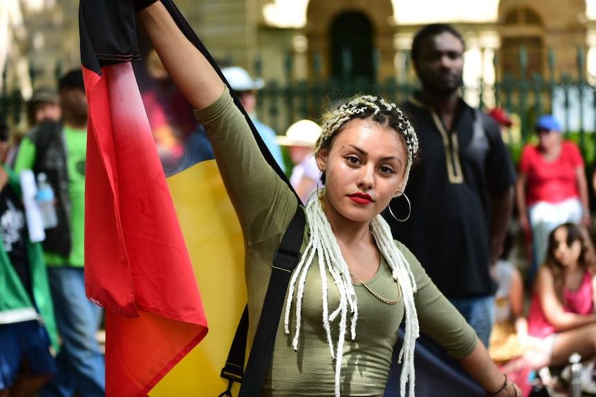 Joy Brimble holds up Australian Aboriginal flag outside Parliament House in Brisbane.