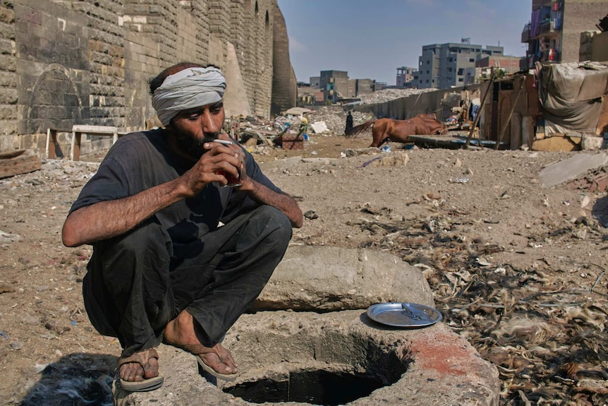 Mohamed, a donkey and horse barber squats while drinking tea and smoking a cigarette
