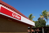 A red Australia Post sign against a blue sky with trees in the background.