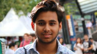 A young man of South Asian background smiles at the camera