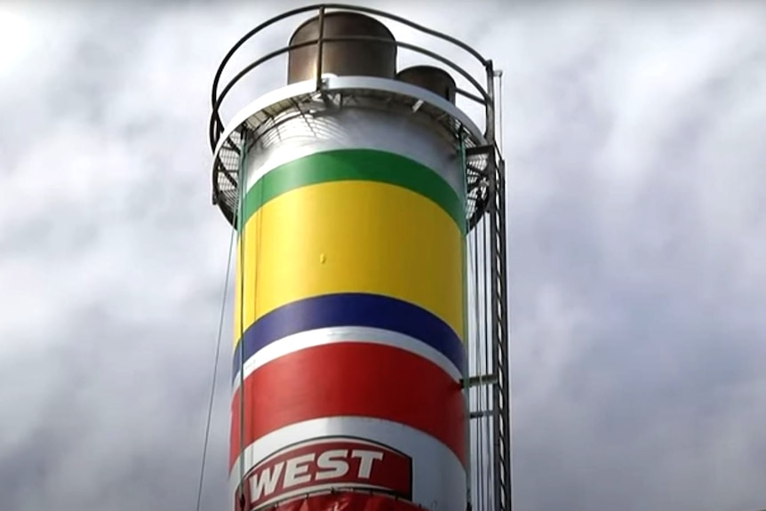 A chimney with green yellow blue white and red paint stripes on it.