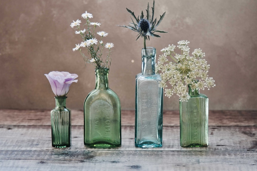 Four green glass bottles containing different flowers