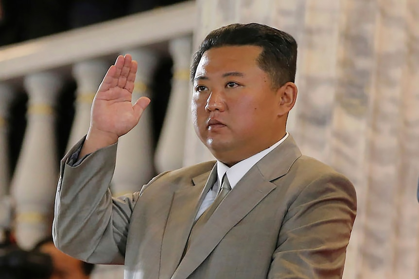 Kim Jong Un stares at something outside the frame, with his hand raised in a salute.