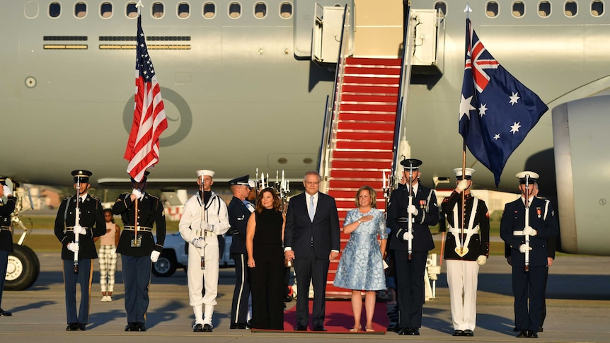 Scott and Jenny Morrison stand with US military personnel at the bottom of a set of aeroplane stairs.