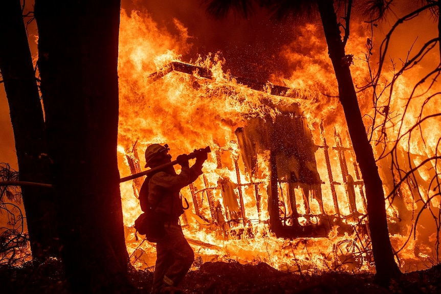 A firefighter in protective gear holds a thick hose over his right shoulder and aims it at a destroyed house still ablaze