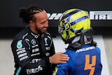 Lewis Hamilton smiles as he greets a helmeted man in yellow and blue near a race track.
