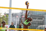 Female volleyball player in green top reaches for ball behind net.