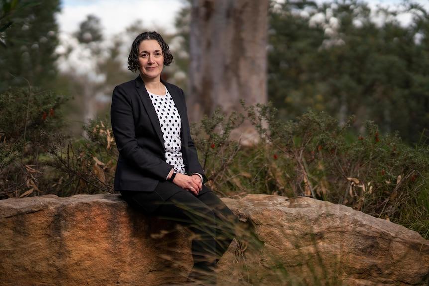 Dr Joelle Gergis sits on a rock