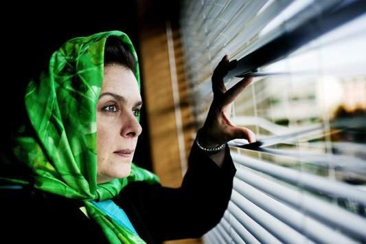 A woman in a head scarf peeks through the blinds.