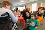 A mother encourages her young child to interact with an elderly aged care resident.