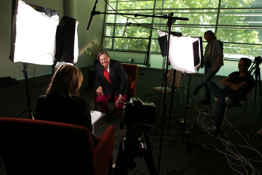 Humphries sitting chair surrounded by lights, camera and sound equipment with crew watching Hutcheon interviewing.