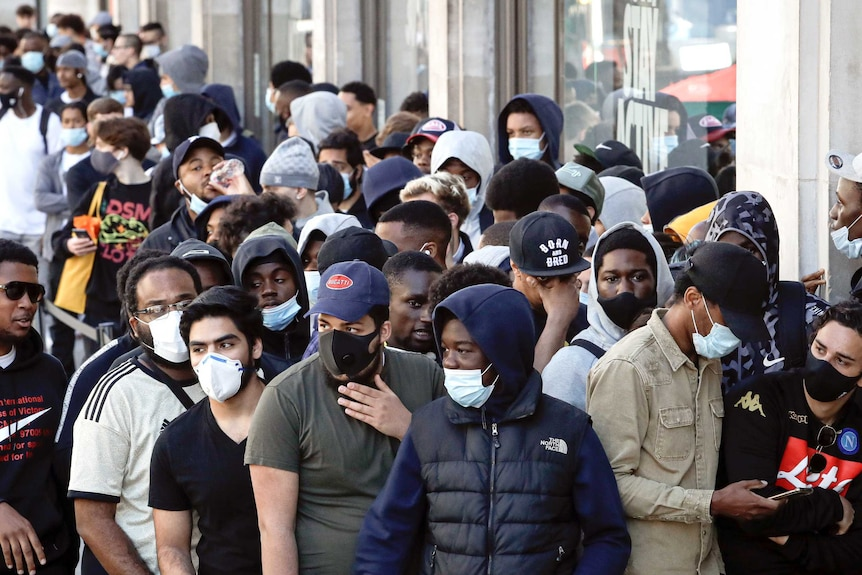 People, some wearing masks, others not, queue outside London stores.