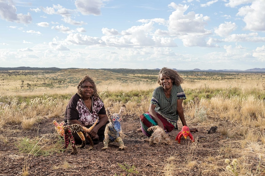 Artists Roma Butler and Yangi Yangi Fox sitting in the Australian outback with sculptures made from native grasses