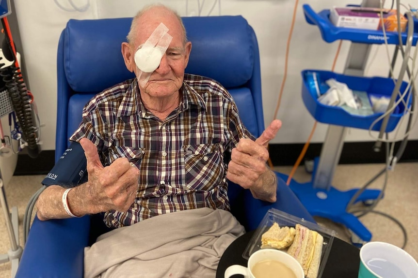 A man in a recovery chair in a hospital ward, one eye bandaged after eye surgery