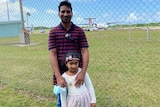 A man smiling as he holds his young daughter in front of an airport fence.