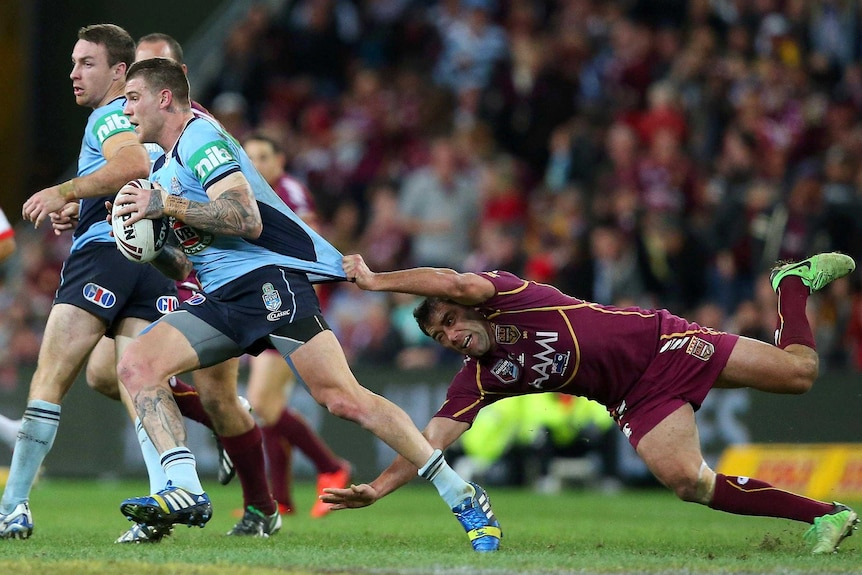 Josh Dugan is tackled by Cameron Smith.