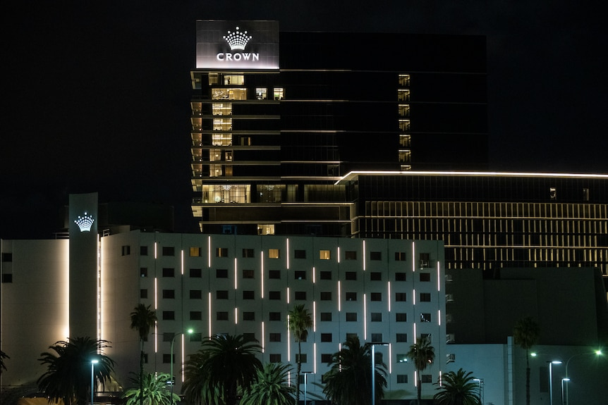 Tall buildings in the dark with lights on with an illuminated sign with the word Crown below a crown symbol.