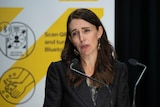Jacinda Ardern behind a lectern speaking at a press conference.
