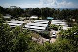 Nibok refugee settlement on Nauru. It is a row of rectangular accommodation units.