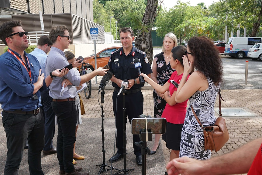 Journalists stand around Police Commissioner Reece Kershaw at a press conference
