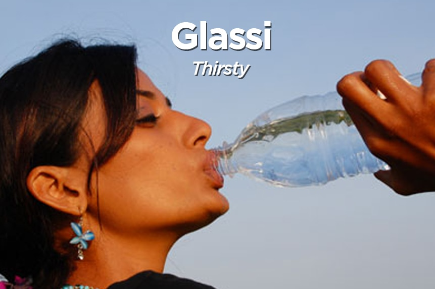 A woman drinks from a bottle of water.