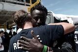 A migrant hugs a crew member from the Aquarius rescue ship