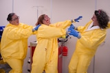 A woman dressed in a biohazard suit attempts to stop a woman in a zombie costume from attacking her male colleague.