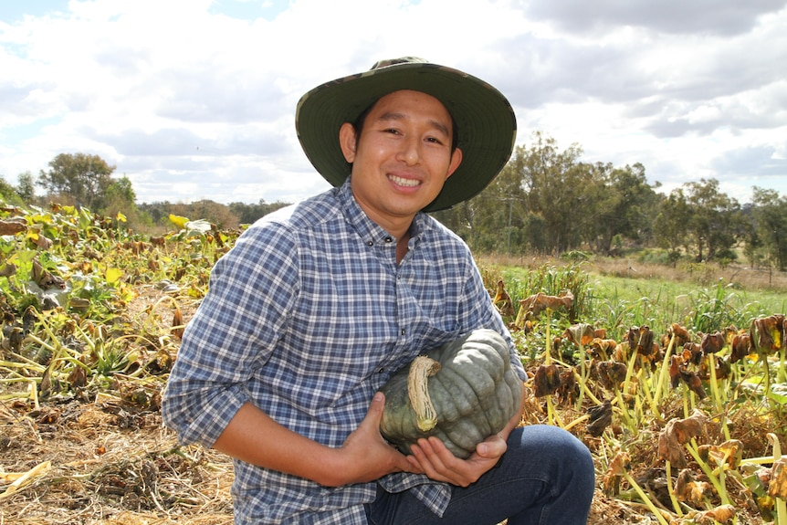 A man holding a pumpkin kneels in a vegetable patch and smiles at the camera.