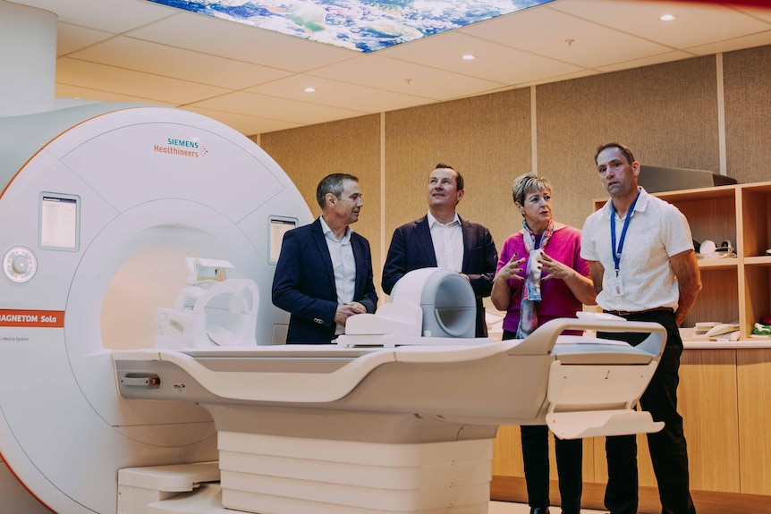 Four people standing behind a new imaging machine in a hospital.
