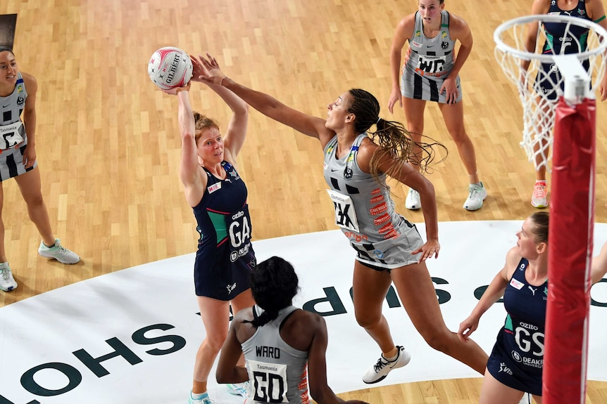 A netballer grimaces as she tries a two-point shot, while a defender stretches her arm out to block.