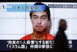 Man walks past image of Kenji Goto