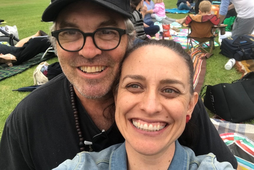 A couple smiling to the camera (selfie) sitting at an outdoor picnic.