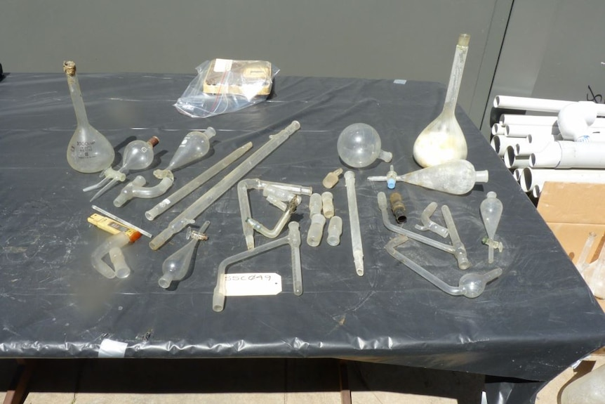 Glass pipes and drug paraphernalia laying on a black table
