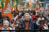 Two men wear masks that bear resemblance to Narendra Modi during a rally in support of India's PM.